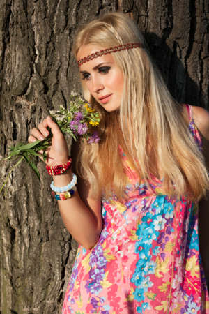 beautiful blonde with flowers stand by tree  style of hippie Stock Photo