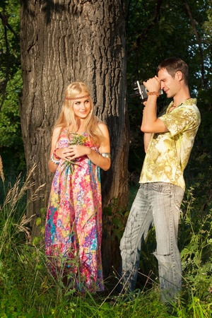 fine blonde with flowers stands by treeand young man holding film camera  style of hippie photo