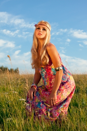beautiful blonde woman posing in meadow against blue sky  style of hippie photo