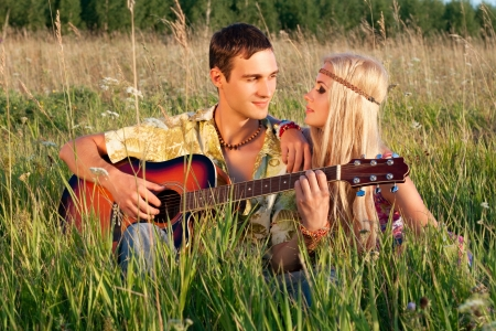 cute young man and fine woman sit on meadow  young man plays  guitar  style of hippie Stock Photo