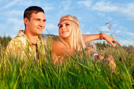 smiling young man and fine woman sit on meadow   style of hippie Stock Photo