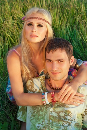 smiling young man and fine woman sit on meadow   style of hippie photo