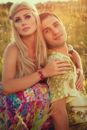 smiling young man and fine woman sit on meadow against sunset   style of hippie photo