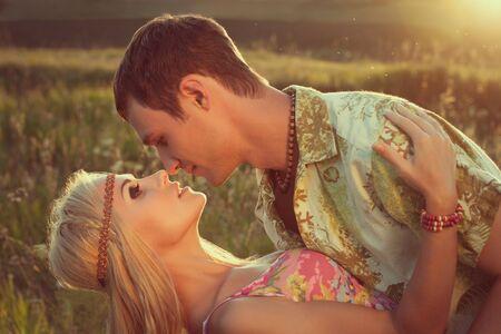 bonsoir: mignons baisers jeune homme belle femme contre le style coucher de soleil de hippie
