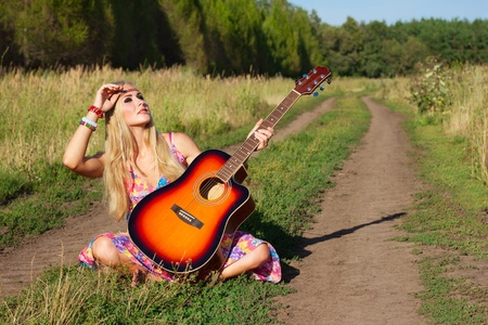 young woman with guitar  hippie hitch-hike