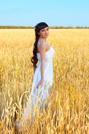 Young smiling woman in white dress in field with wheat Stock Photo