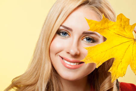 beautiful young  blonde woman holds maple leaf