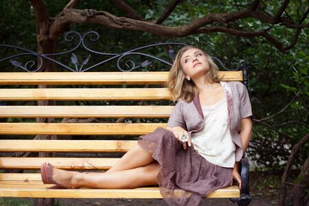 young woman has rest on bench in park