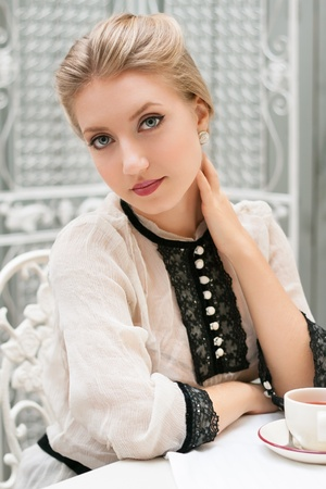 young beautiful woman sits at table with cup  retro style