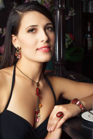 elegant young woman with jewelry in bar photo