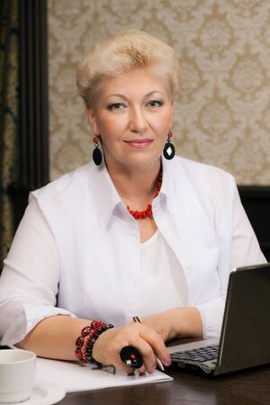 elegant woman with jewelry works at office photo