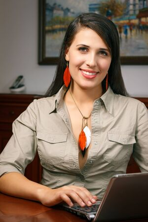 elegant young woman with jewelry works at office Stock Photo
