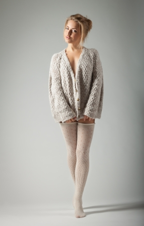 beautiful blond young woman in knitted jumper and stockings stands on gray background photo