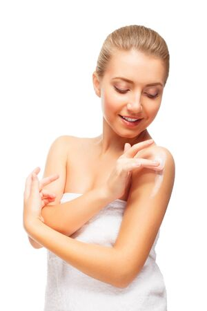 Beautiful blond woman puts moisturizer cream on shoulder. looks at it. isolated on white