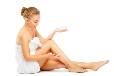 beautiful young blond woman in towel terry puts moisturizer cream on legs, sits on  floor, look down. isolated on white Stock Photo