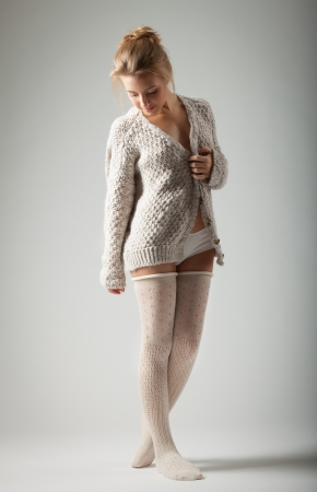 beautiful blond young woman in knitted jumper and stockings stands on gray background Stock Photo