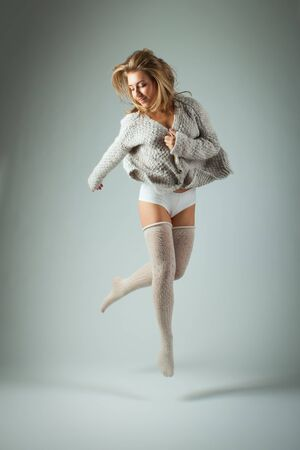 Happy and beautiful young woman jumping high in knitted jumper and stockings on gray background