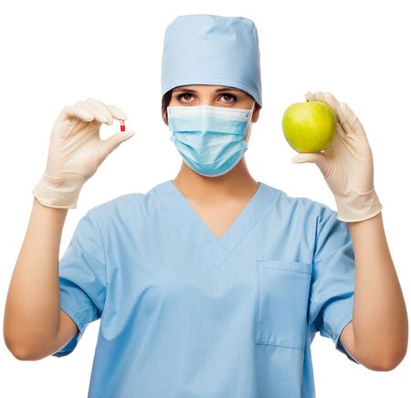 Young doctor holding pill and apple, looking in camera  isolated white background Stock Photo