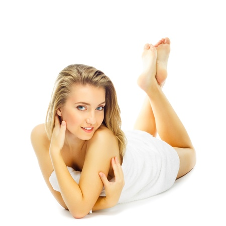 only 1 girl: beautiful young blond woman in towel terry having lifted feet up lies on floor, isolated on white