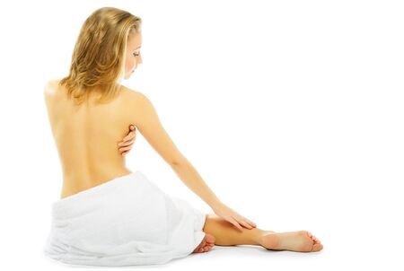 bare attractive blonde woman sitting back to camera looking back with towel around bottom