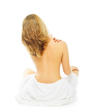 woman in towel: bare attractive blonde woman sitting back to camera with towel around bottom