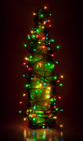 garland on green bottle on dark red background  similar to christmas fir-tree Stock Photo - 18387605