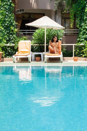young woman has a rest on chaise lounge under umbrella at swimming pool Stock Photo