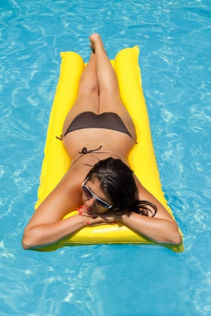 sexy girl floating on a mattress in the sea or swimming pool Stock Photo - 18355231