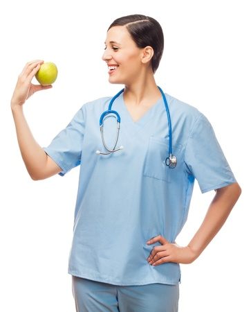 Young doctor holding apple, looking at it  isolated white background
