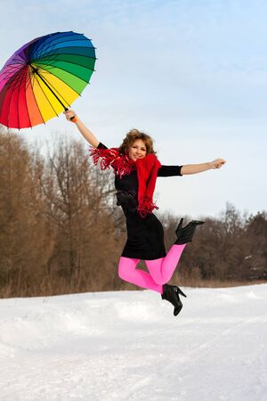 young blond beautiful woman jumping against wood in bright scarf with color umbrella in winter