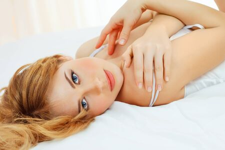 beautiful blond woman lying in bed Stock Photo