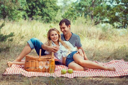 smiling young beautiful couple have a rest in wood on picnic photo