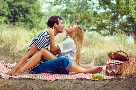 young beautiful couple have a rest in wood on picnic, sitting face to face photo