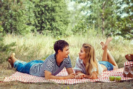 beautiful young couple have a rest in wood on picnic, holding hands, look at each other. Stock Photo - 21307475