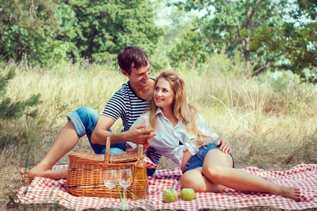 beautiful young couple have a rest in wood on picnic, holding hands photo