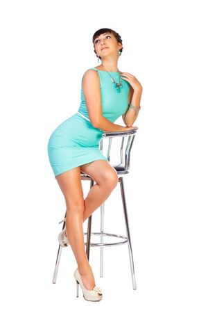woman brunette in turquoise dress sits on chair, white background Stock Photo - 21307486