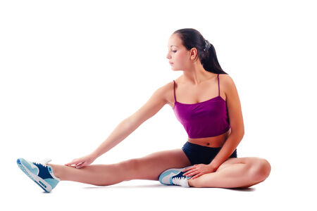 young woman in sportswear does exercises sitting on floor on white