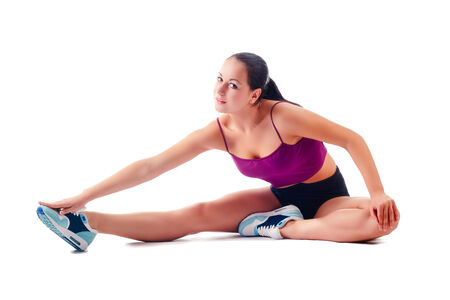 beautiful woman in sportswear does exercises sitting on floor on white background Stock Photo
