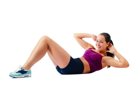 beautiful woman in sportswear does exercises lying on floor on white background