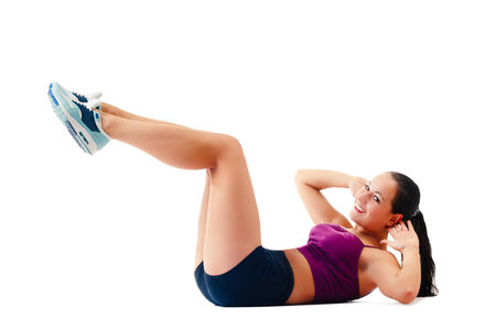 young woman in sportswear does exercises lying on floor on white background