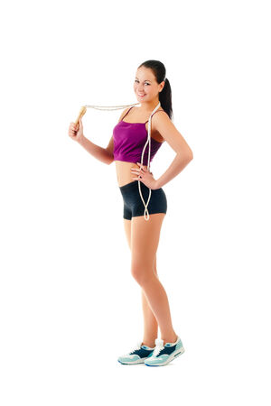 young woman with jump rope on shoulder stand sideways in sportswear isolated on a white