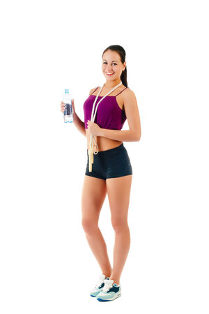 young woman with jump rope on shoulder costs sideways in sportswear keeps bottle with water