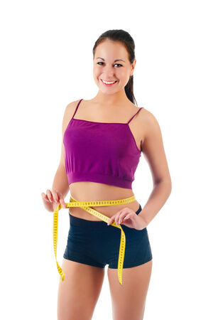 smiling young woman holding a measure tape around her waist isolated on a white