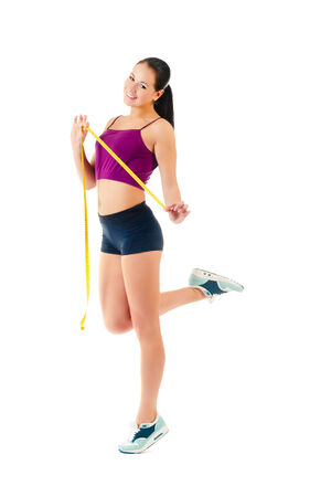young woman holding a measure tape around her waist isolated on a white