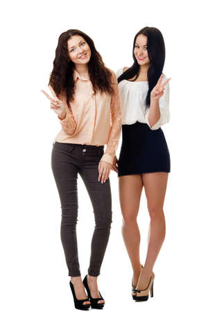 two beautiful young women standing and showing victory sign