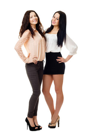 two smiling young women standing embracing each other  isolated on white background