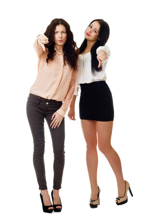 two beautiful young women standing and showing like dislike gesture photo