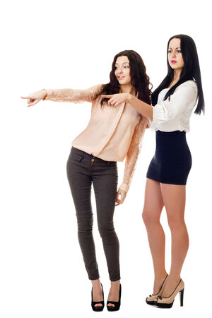 two  standing wonder young women point at something  isolated on white background Stock Photo