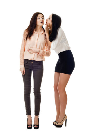 two young beautiful women standing and to whisper to each other Stock Photo