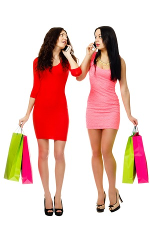 two young shopping women talking by phone isolated on white background